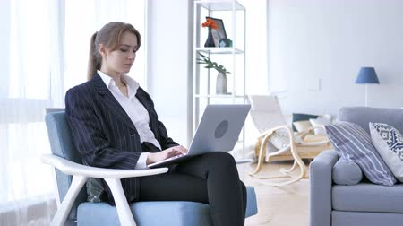use laptop : Young Woman Working On Laptop, Sittting on Sofa inOffice Stock Footage