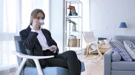 hidratáció : Woman Drinking Coffee while Sitting on Sofa Stock mozgókép
