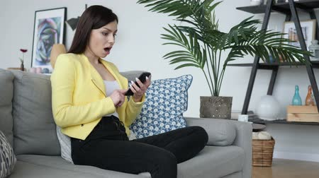 choque : Shocked, Woman Wondering while Using Smartphone Stock Footage