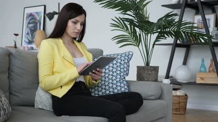 página da internet : Woman Sitting on Sofa Using Tablet for Internet Browsing