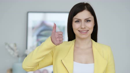 sikerül : Thumbs Up by Young Woman at Work, Looking at Camera Stock mozgókép