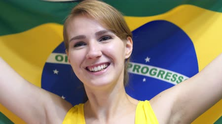 бразильский : Brazilian Young Woman Celebrating while holding the flag of Brazil in Slow Motion
