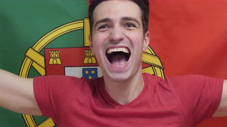 jogador de futebol : Portuguese Young Man celebrities holding the flag of Portugal in Slow Motion