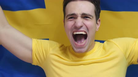 watching : Swedish Young Man Celebrates holding the Flag of Sweden in Slow Motion