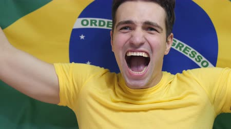 бразильский : Brazilian Young Man Celebrates holding the flag of Brazil in Slow Motion