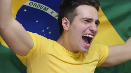 бразильский : Brazilian Young Man Celebrating while holding the flag of Brazil in Slow Motion Стоковые видеозаписи