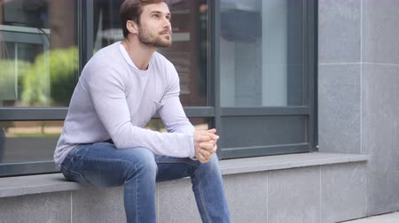 emin : Serious Handsome Man Sitting Outside Office and Looking Around