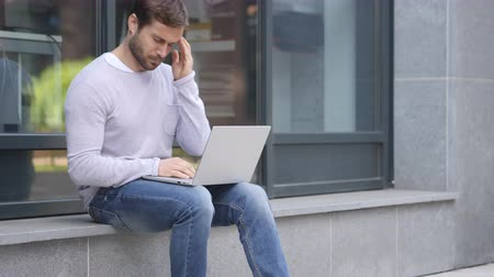 разочарование : Tense Handsome Man with Headache working on Laptop Sitting Outside Office