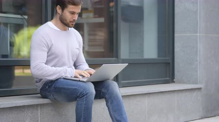 schody : Handsome Man Working on Laptop while Sitting Outside Office