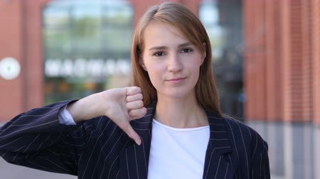 unsuccessful : Thumbs Down by Business Woman at Work Looking at Camera