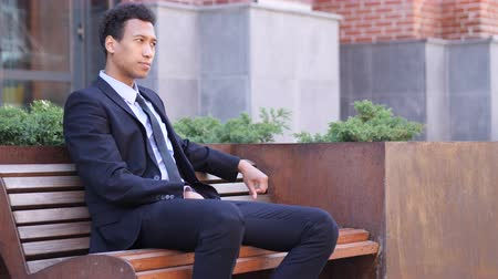 emin : Pensive Serious African Businessman Sitting on Bench Stok Video
