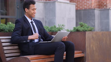 suceder : Excited African Businessman Celebrating Success on Laptop Sitting on bench