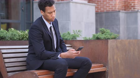 trabalhador de escritório : African Businessman Using Smartphone while Sitting on Bench Stock Footage