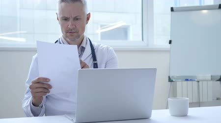 документация : Doctor reading Medical Report of Patient in Clinic