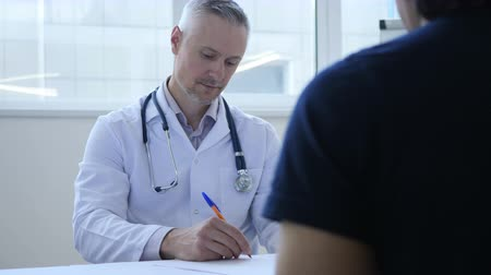 przychodnia : Doctor Writing Medicine to Patient in Clinic