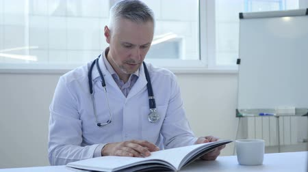 sebész : Doctor Reading Medical Book in Clinic