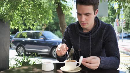 szomjúság : Young Man Mixing Sugar and Drinking Coffee, Sitting in Cafe Terrace Stock mozgókép