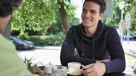 hallgat : Young Man Talking with Friend while Sitting in Cafe Terrace
