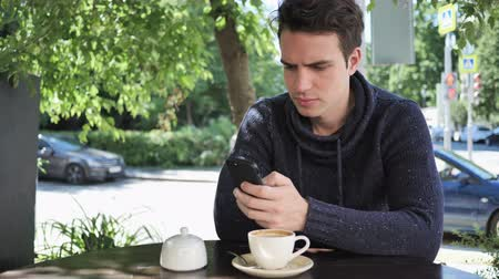 liga : Man Using Smartphone while Sitting in Cafe Terrace Vídeos