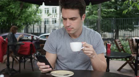 терраса : Man Drinking Coffee and using a Smartphone while Sitting in Cafe Terrace