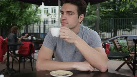 hidratar : Young Man Drinking Coffee while Sitting in Cafe Terrace Stock Footage