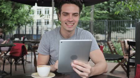 liga : Online Video Chat on Tablet by Man Sitting in Cafe Terrace Vídeos