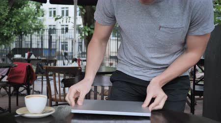 disturbed : Man Coming and Sitting in Cafe Terrace to Work on Laptop Stock Footage