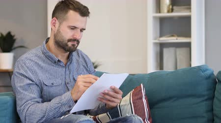 documentation : Man Working on Documents while Sitting on Sofa