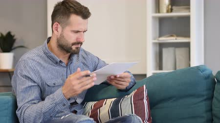 подпись : Penisve Man Reading Agreement, Sitting on Sofa