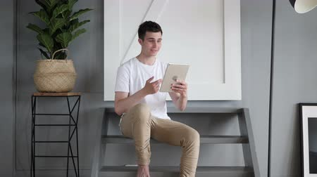 sala konferencyjna : Online Video Chat on Tablet by Man Sitting on Stairs