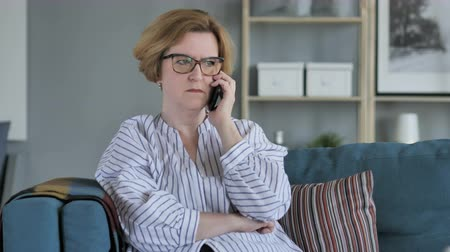 issues : Angry Old Senior Woman Talking on Phone, Sitting on Couch in Bedroom