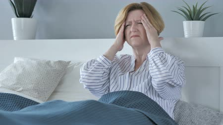 smutek : Upset Old Senior Woman with Headache while Sitting in Bed