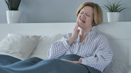 зубы : Toothache, Old Senior Woman with Tooth Pain Sitting in Bed Стоковые видеозаписи