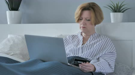 fizet : Online Shopping on Laptop by Old Senior Woman in Bed, Payment Stock mozgókép