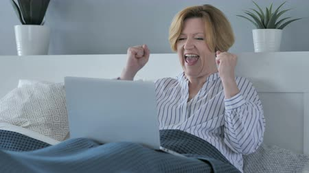nagymama : Reaction of Success by Happy Senior Woman Using Laptop in Bed