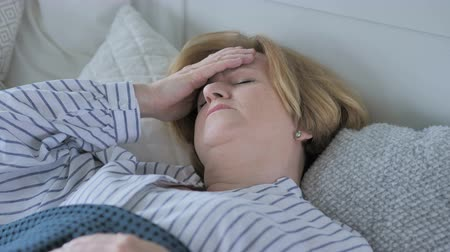 smutek : Upset Old Senior Woman with Headache Sleeping in Bed