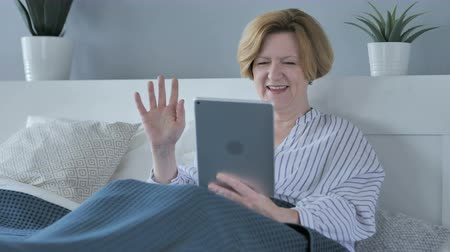 night day : Video chat online sul tablet di stanco vecchia donna anziana a letto