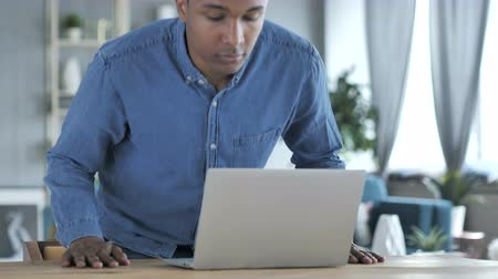 compleição : Young African Man Coming to Work on Laptop