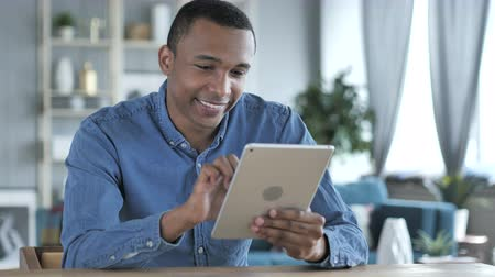 érintés : Young African Man Using Tablet at Workplace