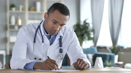 подпись : African-American Doctor Writing Medical Report of Patient, Paperwork