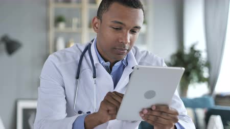 sebész : African-American Doctor Using Tablet for internet Browsing Stock mozgókép