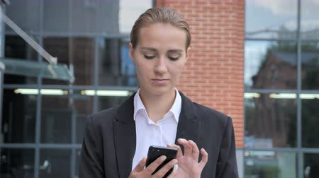 weboldal : Walking Businesswoman Busy Using Smartphone Ouside Office