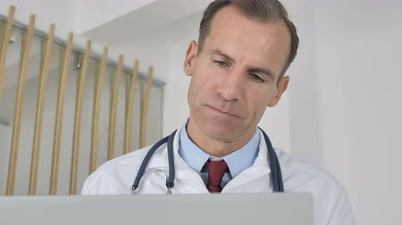 introspection : Pensive Doctor Thinking and Working on Laptop Stock Footage