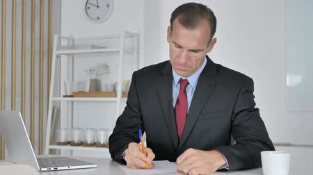 документация : Middle Aged Businessman Writing Documents in Office