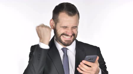 a böngésző : Beard Businessman Excited for Success while Using Smartphone