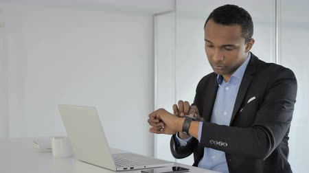 insan parmak : Casual Afro-American Businessman Using Smartwatch for Checking Notifications