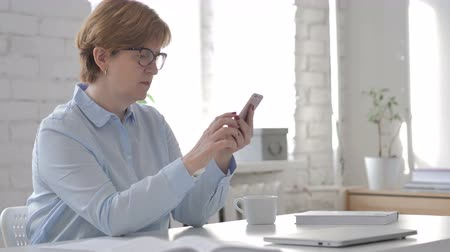 surfing the net : Old Woman Browsing Smartphone Stock Footage