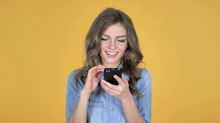 adresa : Young Girl Browsing Smartphone Isolated on Yellow Background