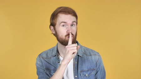 roodharige : Redhead Man Gesturing Silence, Finger on Lips, Yellow Background Stockvideo