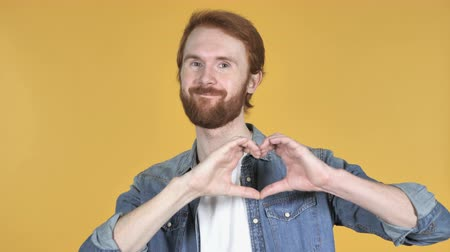 vöröshajú : Handmade Heart by Redhead Man Isolated on Yellow Background